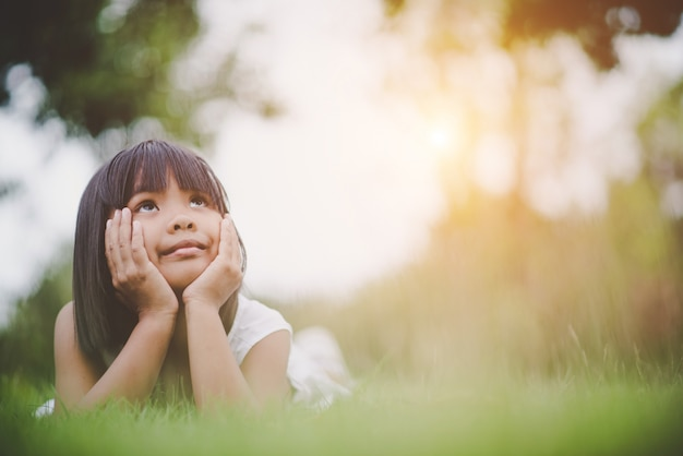 Little girl lying comfortably on the grass and smiling