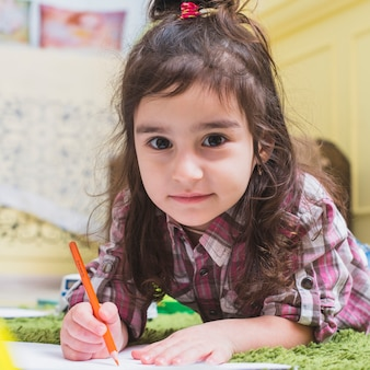 Little girl lying on the floor and drawing Free Photo