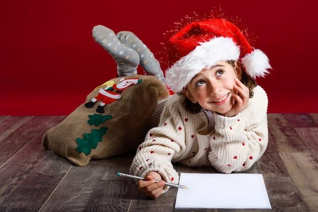 Bambina che si trova sul pavimento sognare svegli con una matita e un foglio