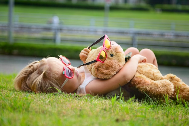 Little girl lying on the grass and hugging a teddy bear