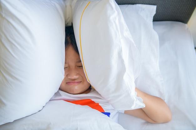 Маленькая девочка лежит в постели, накрывая голову подушкой из-за слишком громкого раздражающего шума. раздраженный ребенок, страдающий от шумных соседей, пытается заснуть после сигнала будильника