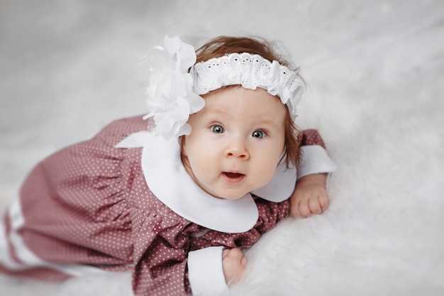 Little girl lying and looking at the camera. beautiful dress and head decoration