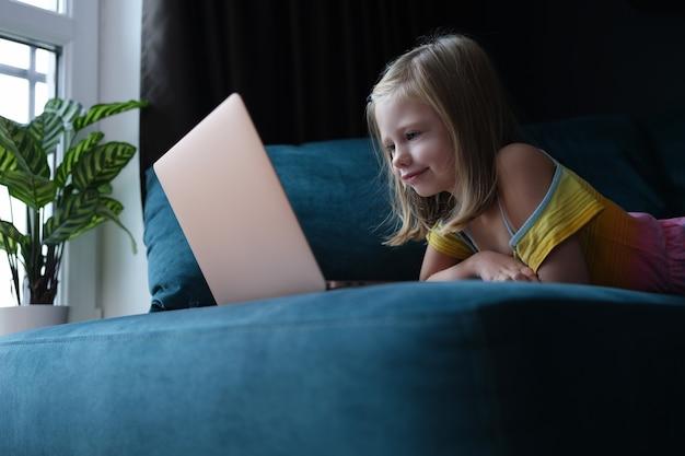 ソファに横になってノートパソコンの画面を見ている少女