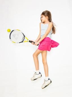 床に横たわって、テニスをするふりをする少女