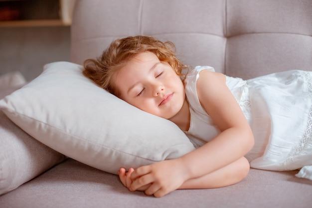 Маленькая девочка, лежа на диване