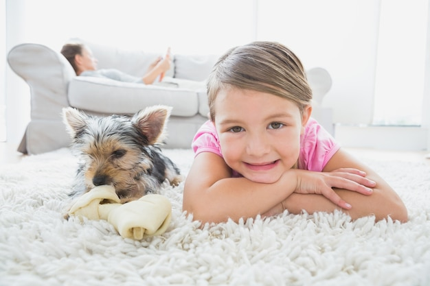 Little girl lying on rug with yorkshire terrier smiling at camera