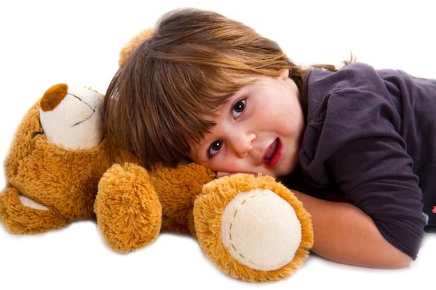 Little girl lying on teddy bear