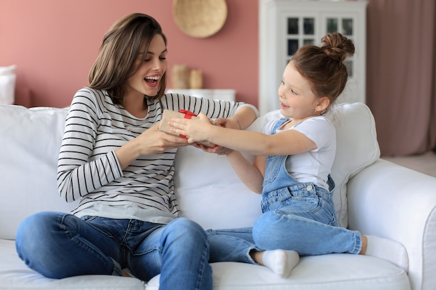 小さな女の子は、お母さんと一緒にソファに座っている間、興奮した親に誕生日プレゼントを作ります。笑顔の小さな子供は、幸せな母親にギフトボックスを贈ります。