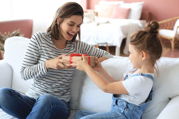 小さな女の子がお母さんと一緒にソファに座っている間、興奮した親に誕生日プレゼントを作り、小さな子供を笑顔で幸せな母親にギフトボックスを贈ります。