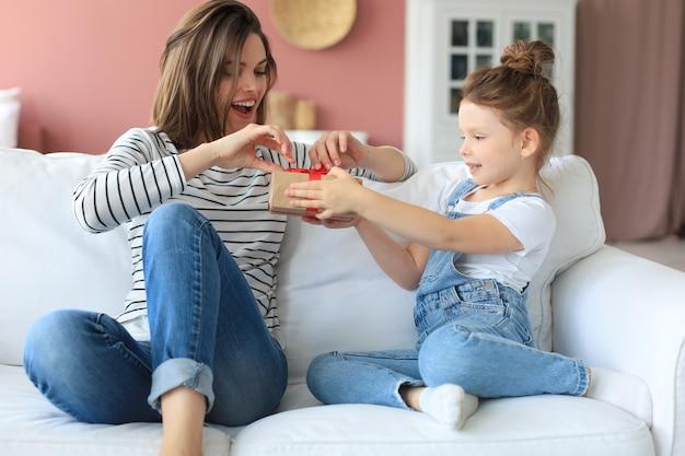 Маленькая девочка делает подарок на день рождения взволнованному родителю, пока они сидят на диване с мамой, улыбающийся маленький ребенок поздравляет подарить подарочную коробку счастливой матери.