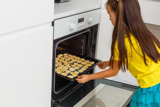 Маленькая девочка сделать печенье во время появления.
