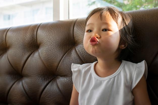 A little girl make fun kissing jokes on sofa