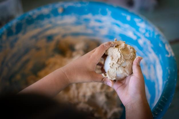 Little girl make salted egg in her hand