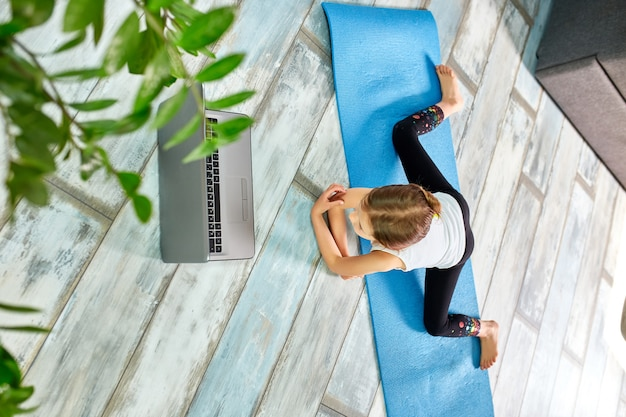 Little girl make workout on blue mat at home by laptop online.