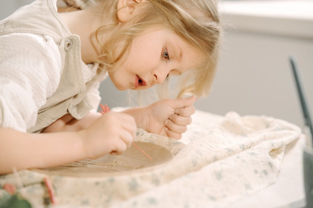 小さな女の子は粘土板を作り、それを飾る