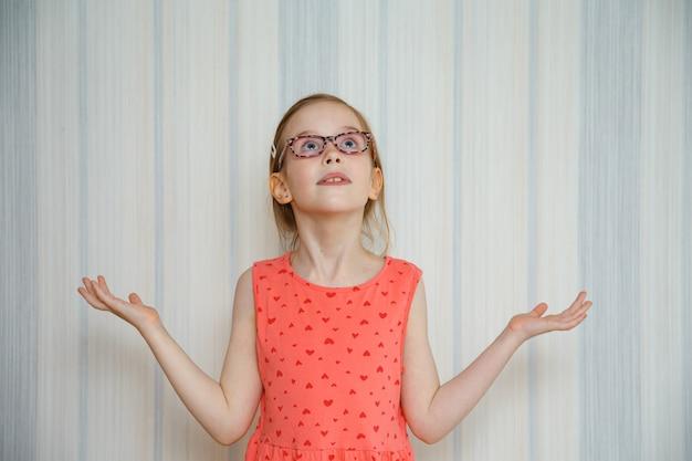 Маленькая девочка делает жест, который ничего не понимает, и смотрит вверх