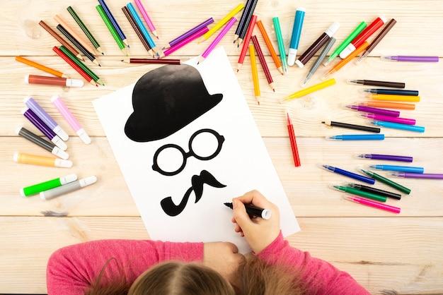 小さな女の子はお父さんやおじいさんにグリーティングカードを作ります Premium写真