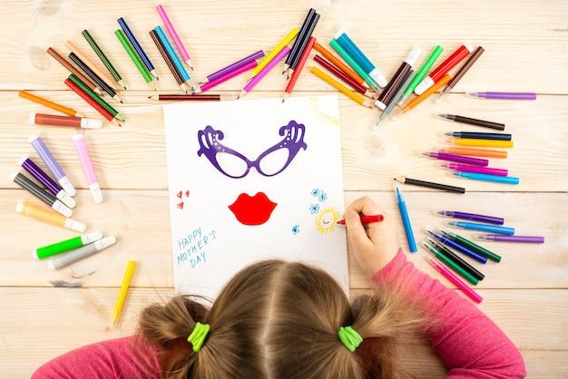 Маленькая девочка делает поздравительную открытку маме с приложением ко дню матери