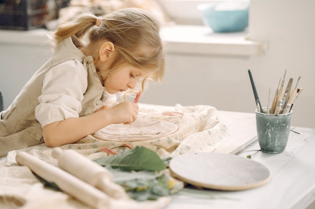 Little girl makes a clay plate and decorates it