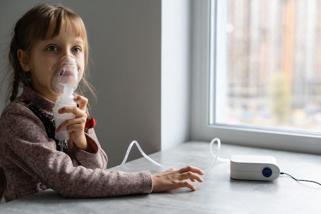 Маленькая девочка делает ингаляцию небулайзером дома, сидя на стуле. переносной аппарат при обструкции, бронхиальной астме.