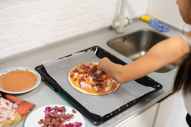 Маленькая девочка делает пиццу дома