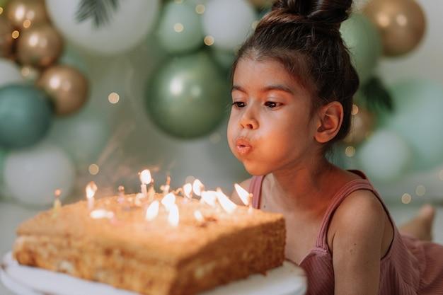 小さな女の子が願い事をして、誕生日を祝うバースデーケーキの女の子にろうそくを吹き消します