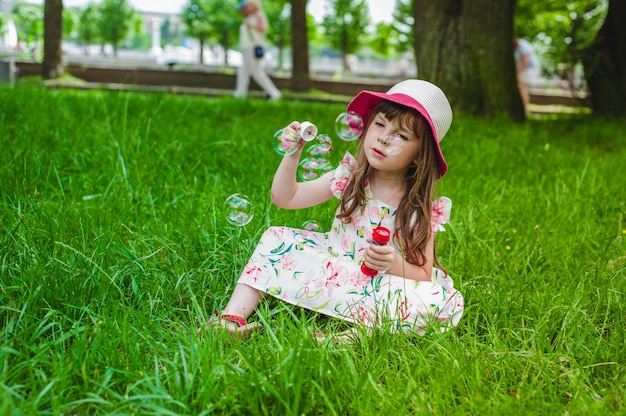 Little girl making bubbles with a pompous