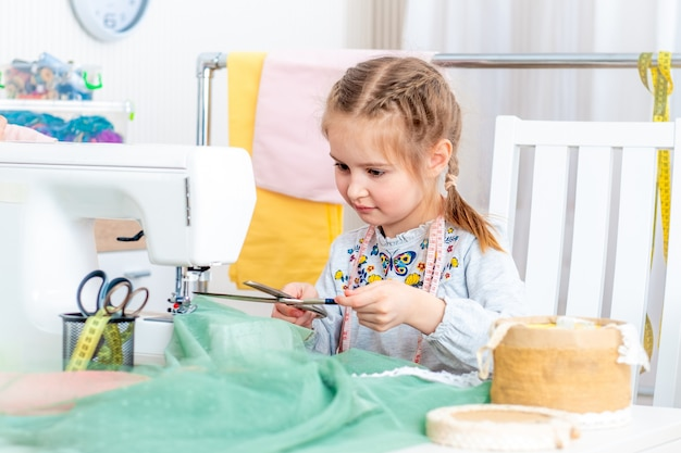 Little girl making crafts at sewing machine