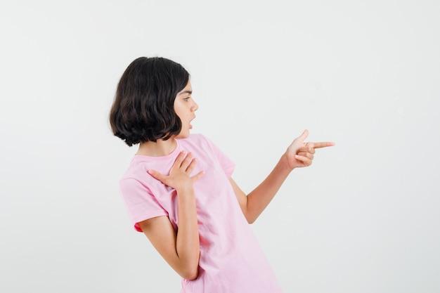 분홍색 티셔츠에 손가락 권총 기호를 만들고 초점을 맞춘 어린 소녀. 전면보기.