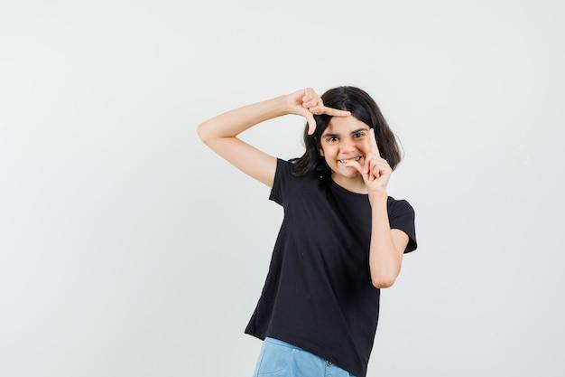 Bambina che fa il gesto del telaio in maglietta nera, pantaloncini e sembra allegro, vista frontale.