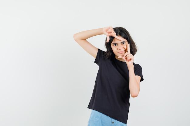 Bambina che fa il gesto del telaio in maglietta nera, pantaloncini e sguardo concentrato. vista frontale.