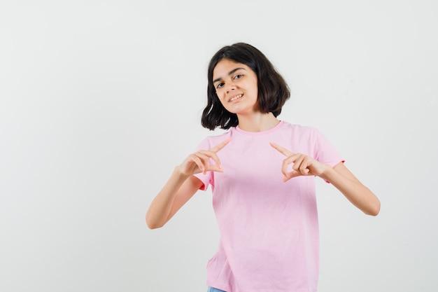 Bambina che fa il gesto del telaio in maglietta rosa e sembra allegra, vista frontale.