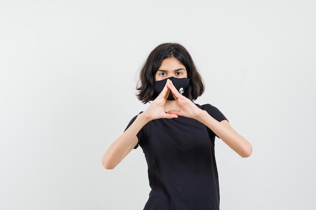 Bambina che fa il gesto del cuore in maglietta nera, maschera e guardando fiducioso, vista frontale.