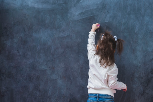 Little girl making line with chalk