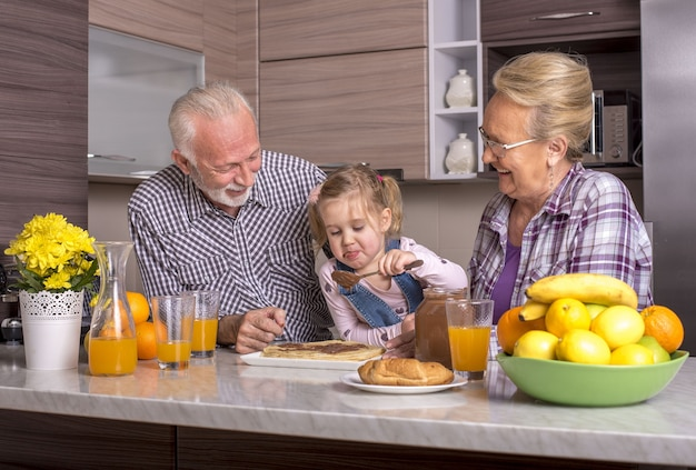 Little girl making pancakes with her grandparents