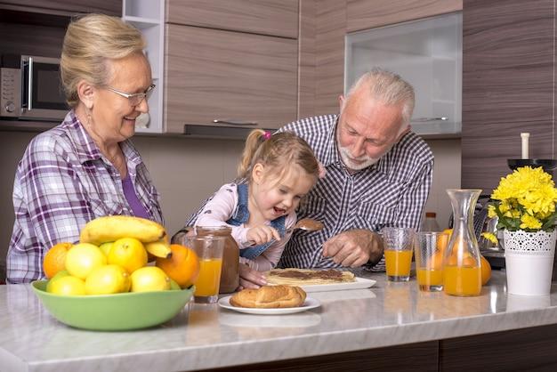 祖父母と一緒にパンケーキを作る少女