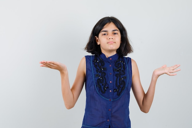 Little girl making scales gesture in blue blouse