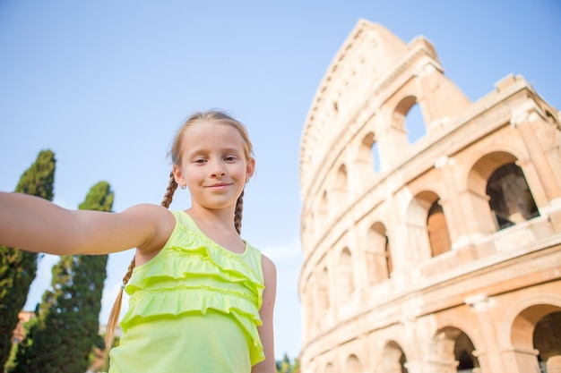 Little girl making selfie background coliseum, rome, italy. kid portrait at famous places in europe