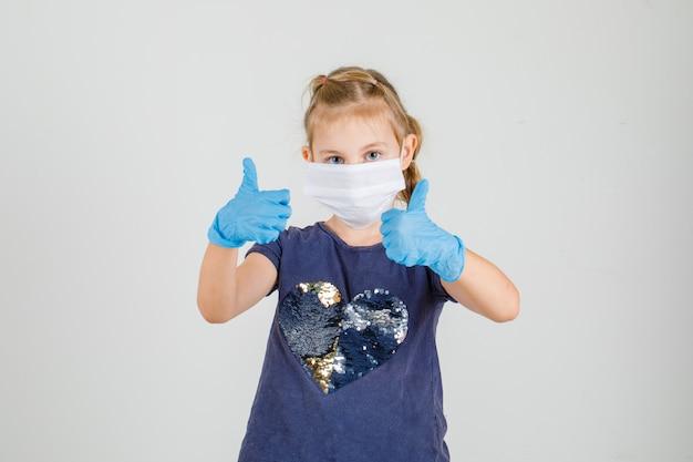 Tシャツ、手袋、医療用マスクで親指を立て、自信を持って探している少女。正面図。