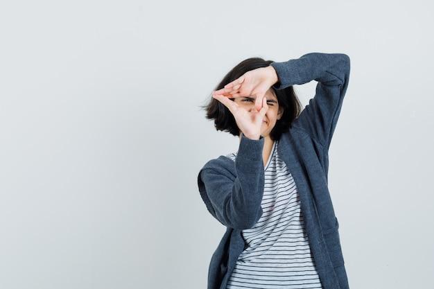 Bambina che fa il gesto del triangolo in t-shirt, giacca e guardando fiducioso.