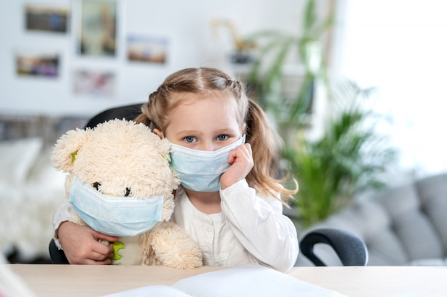 Little girl in a mask , hugging a teddy bear, looking sad, concept of e-learning