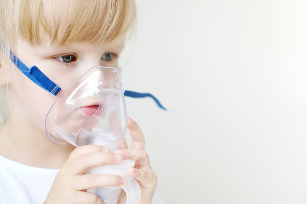 Little girl in a mask for inhalations, making inhalation with nebulizer at home inhaler on the table, indoor, sick child