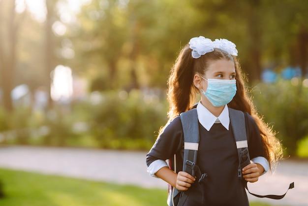 Little girl in medical mask back to school. schoolgirl wearing medical face mask.