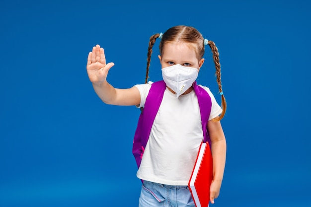 Little girl in a medical mask makes a stop gesture