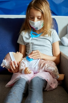 A little girl in medical mask sits on the sofa, plays a doctor, treats and listens to the doll with a stethoscope in a medical mask, at home during quarantine and pandemic