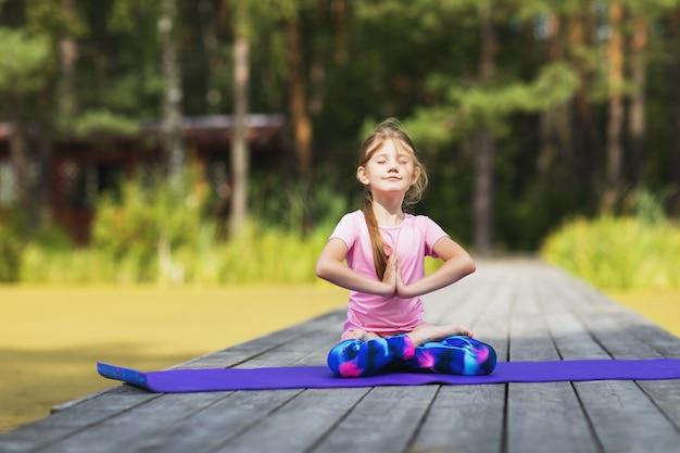 Маленькая девочка медитирует в парке, сидя в позе лотоса на деревянном мосту в летний день
