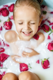 Little girl in milk bath with red roses