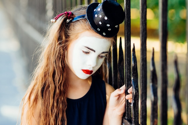 Little girl mime is sad standing at the fence