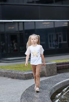 도시 광장에서 걷는 어린 소녀 모델.