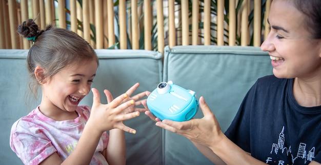 즉석 사진 인쇄를 위한 어린 소녀, 엄마, 장난감 디지털 카메라.